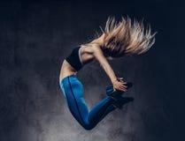 A bailarina loura nova no sportswear dança e salta em um estúdio Isolado em um fundo escuro fotografia de stock