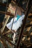 A bailarina macia está sentando-se em uma escada oxidada velha imagens de stock