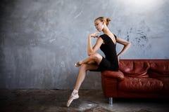 A bailarina magro super em um vestido preto está levantando no estúdio Imagem de Stock