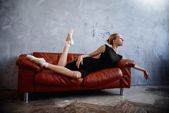 A bailarina magro super em um vestido preto está levantando no estúdio Foto de Stock Royalty Free