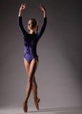 Bailarina no equipamento azul que levanta nos dedos do pé, mãos acima imagem de stock