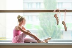 Bailarina no vestido cor-de-rosa que senta-se no janela-peitoril Imagens de Stock