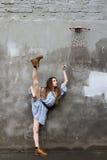Bailarina no vestido e botas perto de um muro de cimento Fotos de Stock