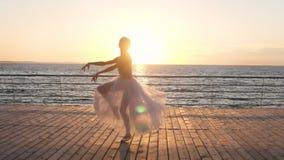 A bailarina nova bonita pratica sua técnica, fazendo o pas clássico do bailado, saltando Paisagem do mar e do sol no video estoque