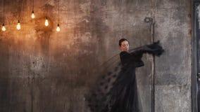 A bailarina nova está dançando em um fundo cinzento da parede do vintage velho video estoque