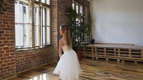 A bailarina nova executa um balé clássico em sapatas e em tutu do pointe no fundo de uma grande janela e de um tijolo vermelho filme