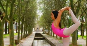 Bailarina nova que estica seu pé ao dançar no parque 4k filme
