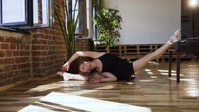 Bailarina nova que faz esticando o assento em um assoalho Ginasta para treinar A menina atrativa no tutu preto está fazendo filme