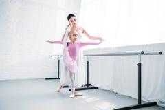 bailarina pequena adorável no tutu cor-de-rosa que exercita com professor fotografia de stock