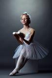 Bailarina pequena de sorriso que levanta o assento no cubo Imagens de Stock