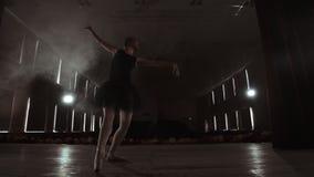Bailarina profesional joven que hace los movimientos circulares en etapa Baile hermoso de la muchacha en proyectores por la tarde metrajes