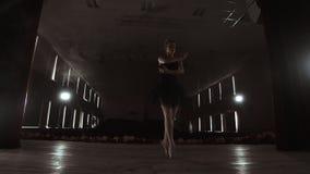Bailarina profissional nova que faz movimentos circulares na fase Dança bonita da menina nos projetores na noite durante vídeos de arquivo