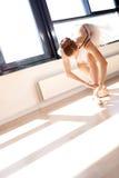 Bailarina que amarra laços de deslizadores do bailado no estúdio Fotos de Stock Royalty Free