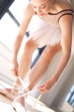 Bailarina que amarra laços de sapatas de bailado no estúdio Imagens de Stock