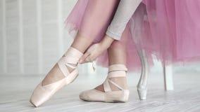 Bailarina que amarra os pointes sapatas de bailado vestindo do dançarino de bailado no estúdio filme