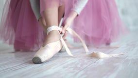 Bailarina que amarra os pointes sapatas de bailado vestindo do dançarino de bailado no estúdio vídeos de arquivo