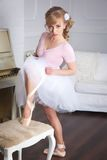 Bailarina que amarra sapatas de Pointe Fotografia de Stock Royalty Free