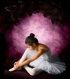 Bailarina que ata el pointe de las cintas fotos de archivo