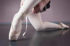 Bailarina que ata la cinta en sus deslizadores del ballet fotografía de archivo libre de regalías