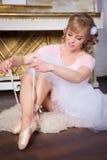 Bailarina que ata los zapatos de Pointe Fotos de archivo libres de regalías