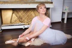 Bailarina que ata los zapatos de Pointe Imágenes de archivo libres de regalías