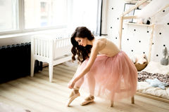 Bailarina que ata los zapatos de Pointe Fotografía de archivo
