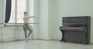 Bailarina que executa o exercício pied de sur le cou de vídeos de arquivo