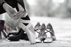 Bailarina que põe sapatas de bailado de Pointe sobre seus pés Fotografia de Stock