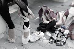 Bailarina que pone los zapatos de ballet de Pointe en sus pies Imagen de archivo
