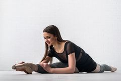 Bailarina que pratica no assoalho de seu estúdio da arte fotografia de stock