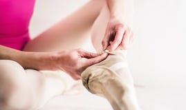 Bailarina que prepara suas sapatas de bailado Imagens de Stock