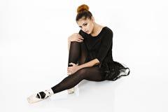 Bailarina que presenta en el piso en un blanco Fotografía de archivo