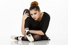 Bailarina que presenta en el piso en un blanco Imagenes de archivo