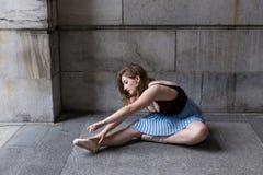 Bailarina que se sienta en perfil en el pórtico de piedra que estira sobre sus zapatos del pointe foto de archivo libre de regalías