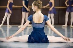 Bailarina que senta-se no assoalho com o o seu de volta à câmera no th Foto de Stock