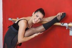 Bailarina que sorri ao esticar o pé na barra do bailado foto de stock royalty free