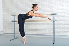 Bailarina que wrming acima da barra próxima no estúdio do bailado, retrato completo do comprimento foto de stock