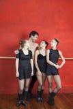 Bailarinas de Standing Arms Around do instrutor no estúdio foto de stock royalty free