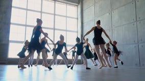 Bailarinas hermosas en tutúes negros en una lección del ballet Danza preciosa de las muchachas en la escuela del ballet Demostrac almacen de metraje de vídeo