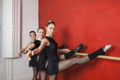 Bailarinas novas seguras que esticam na barra Fotos de Stock Royalty Free