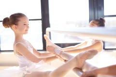 Bailarinas pequenas que esticam seus pés usando a barra Fotos de Stock Royalty Free