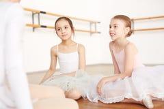 Bailarinas pequenas que sentam-se no assoalho e que escutam fotografia de stock
