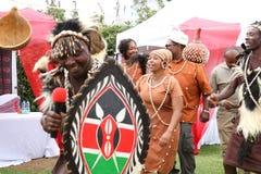 Bailarines africanos vestidos en la regalía tradicional que canta en una ceremonia de boda del kikuyu en Kenia imágenes de archivo libres de regalías