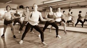 Bailarines alegres del principiante que aprenden elementos del zumba foto de archivo