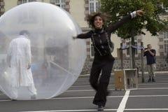 Bailarines con una esfera transparente Imágenes de archivo libres de regalías