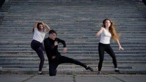 Bailarines contemporáneos que hacen muchachas al aire libre, dos de la demostración y un baile del hombre en el cuadrado metrajes