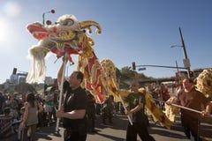 Bailarines de oro del dragón del desfile del dragón Fotos de archivo libres de regalías