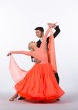 Bailarines del salón de baile con el vestido anaranjado - extensión de los brazos Foto de archivo