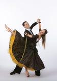 Bailarines del salón de baile con el vestido negro que golpea la pierna con el pie Imágenes de archivo libres de regalías