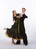 Bailarines del salón de baile con la pierna negra del vestido levantada Imagenes de archivo